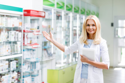 smiling woman pharmacist holding tablet